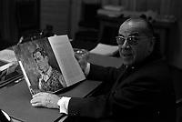 """23 février 1967. Plan en buste de Monsieur Louis Izar, Directeur général du Théâtre du Capitole, assis à son bureau, tenant entre ses mains un livre représentant une reproduction de l'autoportrait du compositeur George Gershwin. Observation: Répétion, au Théâtre du Capitole de l'opéra américain """"Porgy and Bess"""", Musique de geoge Gershwin, à l'occasion du 30ème anniversaire de sa mort."""