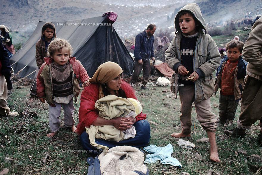 Kurdistan Irak 1991.Une femme et ses enfants épuisés à la frontière Irak-Turkey, sur le chemin de l'exil..Iraki Kurdistan 1991.On the way to exile, a woman and her children exhausted at the border Iraq-Turkey
