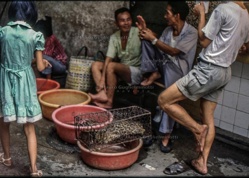 una bambina indica un animale selvatico in gabbia  al mercato alimentare di Canton