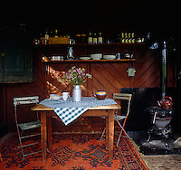 The simple interior of the fishing lodge has a small wood-burning stove for making tea and a wooden table with a pair of garden chairs