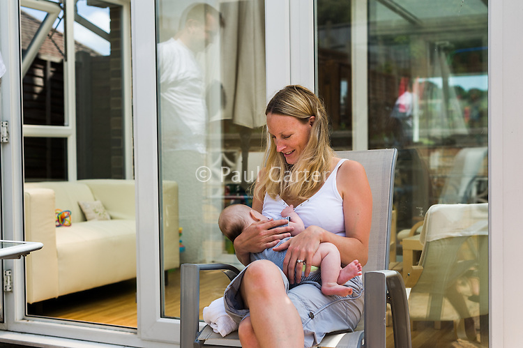 A woman sitting in a patio chair outside her conservatory and breastfeeding her baby wilst her husband looks on reflected in the glass.<br /> <br /> 09/07/2011<br /> Hampshire, England, UK