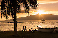 A visiting couple walks along on a Maui beach as the sun sets behind Lana'i.