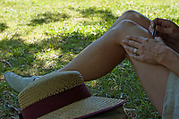 Woman removing hair from her legs with tweezers, France.