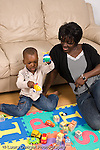 2 year old toddler boy with mother interaction playing with toys language development mother talking and involved African American vertical