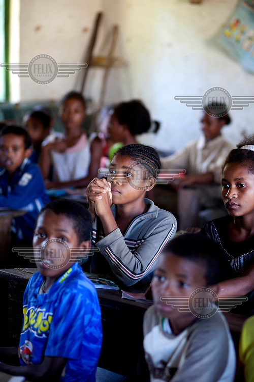 13 year old Saholinirine Ernestine sits among fellow pupils at a school near her home in Miakadaza Fokontany.