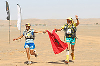 8th October 2021; Boulchrhal to Sud Jebel Irhfelt N'Tissalt ;  Marathon des Sables, stage 5 and final stage of  a six-day, 251 km ultramarathon, which is approximately the distance of six regular marathons. The longest single stage is 91 km long. This multiday race is held every year in southern Morocco, in the Sahara Desert. Aziz Raji (mor) crosses the line as ladies winner holding hands with compatriot HAMDOUCH Hassna (Mor)