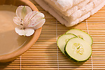 Mud mask and slices of cucumber on bamboo mat