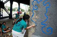 """Ali Grotkowski paints a mural under a train bridge during """"Circle the City with Service,"""" the Kiwanis Circle K International's 2015 Large Scale Service Project, on Wednesday, June 24, 2015, in Indianapolis. (Photo by James Brosher)"""