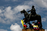 BOGOTA, COLOMBIA - MAY 01 : Demonstrators climb in a local monument as they protest against tax reform during the International Workers' Day on May 01, 2021 in Bogota, Colombia. Hundreds of Colombians protest against a tax bill reform plan for the fourth day in a row which aimed to raise some $ 6.3 billion in additional revenue over 10 years for Colombia, which saw GDP fall 6.8 percent in 2020 .(Photo by Leonardo Munoz/VIEWpress)