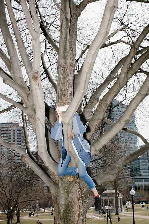 A person takes pictures from a tree during the March For Our Lives protest and demonstration in Boston Common in Boston, Massachusetts, USA, on Sat., March 24, 2018. The march was held in response to recent school gun violence.