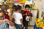 Education preschool 3 year olds group playing in pretend play area boy holding toy phone to doll's ear,, gir using camera, boy with phone looking on, playing separately and together