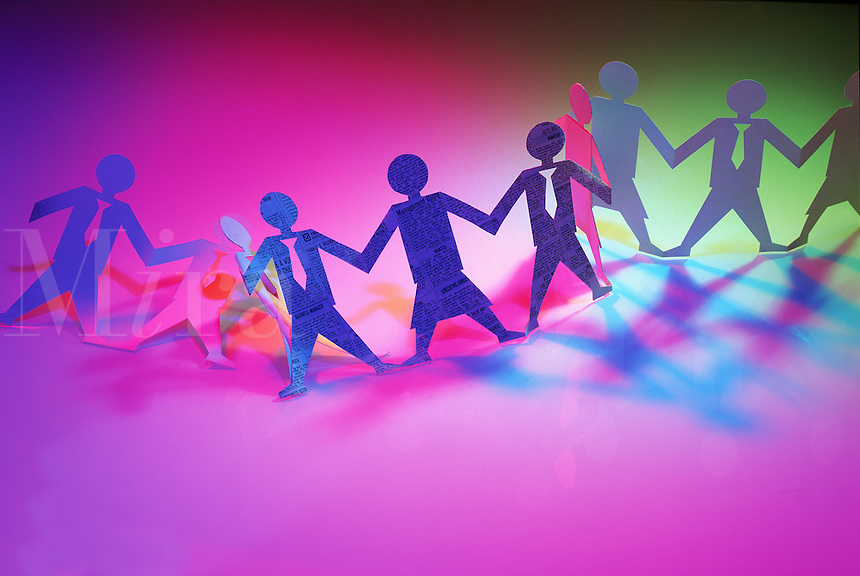 Paper dolls wearing business suits hold hands in a multicolored, spotlit background. Concept; team work and cooperation.