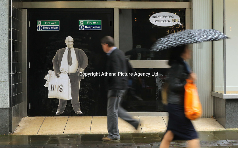 """Pictured: Shoppers walk past a poster of Sir Philip Green on the door of the now closed down BHS store in Oxford Street, Swansea, Wales, UK. Tuesday 13 September 2016<br /> Re: Former owner of BHS, Sir Philip Green has paid a surprise 'visit' to the closed down BHS store in Swansea.<br /> He was spotted in the doorway of the Oxford Street store, which closed its doors for the last time last month.<br /> In his hand was a BHS shopping bag with money spilling out of it.<br /> Sir Philip had owned BHS before selling it for £1 last year.<br /> He is claimed to have taken millions out of the company in dividends and left behind a £571m pensions deficit.<br /> Alongside the poster are the words: """"Thankyou for your custom Sir""""."""