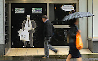 "Pictured: Shoppers walk past a poster of Sir Philip Green on the door of the now closed down BHS store in Oxford Street, Swansea, Wales, UK. Tuesday 13 September 2016<br /> Re: Former owner of BHS, Sir Philip Green has paid a surprise 'visit' to the closed down BHS store in Swansea.<br /> He was spotted in the doorway of the Oxford Street store, which closed its doors for the last time last month.<br /> In his hand was a BHS shopping bag with money spilling out of it.<br /> Sir Philip had owned BHS before selling it for £1 last year.<br /> He is claimed to have taken millions out of the company in dividends and left behind a £571m pensions deficit.<br /> Alongside the poster are the words: ""Thankyou for your custom Sir""."