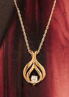 Gold and diamond necklace against red stained glass