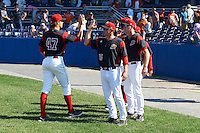 Batavia Muckdogs pitcher Jordan Hillyer (47) high fives coaches Chad Rhoades (15), T.J. Gamba (21), and manager Angel Espada (hidden) during a game against the Auburn Doubledays on September 5, 2016 at Dwyer Stadium in Batavia, New York.  Batavia defeated Auburn 4-3. (Mike Janes/Four Seam Images)