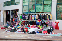 Myanmar, Burma. Mandalay.  Clothing Store Goods Spill out of the Store on to the Sidewalk in Downtown Mandalay.