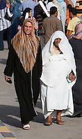 Tripoli, Libya, North Africa - Libyan Women at International Trade Fair.  Clothing Styles, Modern on Left, Traditional on Right.  Older Women Commonly Clasp their Furashiya (light white outer garment) in their Teeth to ensure that it covers more of their body.