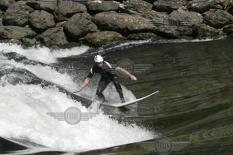 Nestled amongst snowcapped mountains,  and over 100 kilometers from any saltwater, the village of Voss may seem an unlikely spot for surfing. That doesn't stop a group of  of local surfers who has found several spots in rivers nearby...Veteran kayaker, Einar Raa Nilsen (with helmeet) , surf the river he has paddled for many years. © Fredrik Naumann