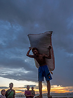 Dramatic sunset and an approaching storm at the banks of the Irrawaddy River in Mandalay Unloading boats at the last light of the day Carrying a heavy load,