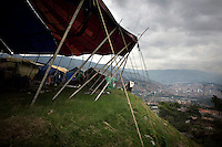 The big top of Jhon Danyer Circus and and the city of Medellin seen from the Robledo Aures neighbourhood. Around a dozen small circuses wander the poorer neighbourhoods around the city of Medellin putting on performances in what can be a hand to mouth existence. Despite falling audience numbers, new health and safety regulations and other bureaucracy these small family businesses, many of whom have existed for generations, still scrape a living in a world where the people are more accustomed to being entertained by soap operas than by live entertainment.