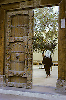 Kuwait April 1967.  Old Doorway leading to Interior Courtyard of a Private Residence, with Man Entering. AN ADDITIONAL 100 HISTORIC IMAGES OF KUWAIT MADE BETWEEN 1966-1972 ARE AVAILABLE.  LET US KNOW WHAT YOU NEED.
