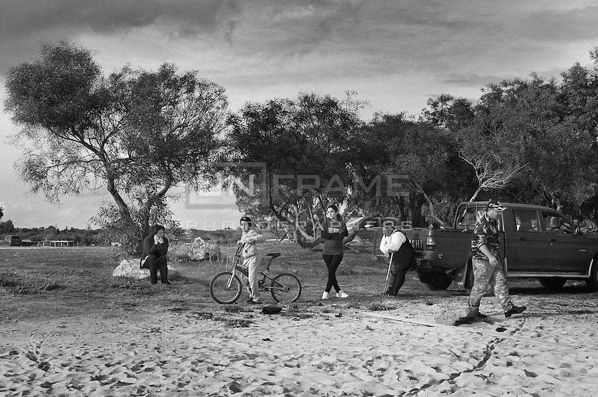 A family waits on the beach for the return of one of their sons which has gone fishing