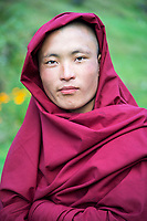 Portrait of a young buddhist monk in red robes at Dungdung Ngesa, Central Bhutan