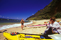 Woman walking on Milolii Beach, with man and kayaks, Na Pali Coast, Kauai