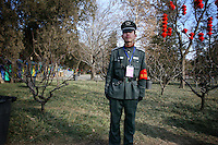 CHINA. A security guard during Chinese New Year in Ditan Park in Beijing.  Chinese New Year, or Spring Festival, is the most important festival and holiday in the Chinese calendar In mainland China, many people use this holiday to visit family and friends and also visit local temples to offer prayers to their ancestors. The roots of Chinese New Year lie in combined influences from Buddhism, Taoism, Confucianism, and folk religions.  2008.