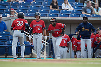 Johan Lopez (32) of the Charleston RiverDogs is greeted by teammates as he returns to the dugout after hitting a home run against the Kannapolis Cannon Ballers at Atrium Health Ballpark on June 30, 2021 in Kannapolis, North Carolina. (Brian Westerholt/Four Seam Images)