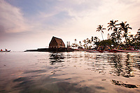 Sunset with reflections of palm trees in the water at Ahuena heiau, an ancient Hawaiian temple on the bay at Kailua-Kona, Big Island. Canoe paddlers glide along the coastline.