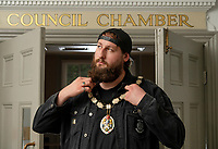 BNPS.co.uk (01202) 558833<br /> Pic: ZacharyCulpin/BNPS<br /> <br /> Pictured: Punk rock Mayor Andy Wrintmore  in the of the Frome Council Chamber<br /> <br /> At 6ft 9in tall, dressed all in black, with a big beard and wearing wayfarer shades, Andy Wrintmore does not look like your typical mayor.<br /> <br /> But the 29-year-old hardcore punk rock drummer is a big hit with old and young constituents in his hometown of Frome, Somerset.<br /> <br /> Andy, a member of punk band SickOnes, was elected to the town council by a landslide vote in 2019 and chosen to become the town's mayor in May this year.<br /> <br /> He has earned the moniker the 'punk rock mayor of Frome' and has even been interviewed by Kerrang magazine about his new career - cutting ribbons and meeting local community groups.