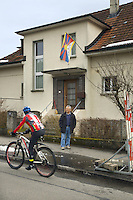 "Switzerland. Canton Bern. Muri. Thubten Purang stands on the sidewalk in front of his home where he has hanged a tibetan flag. A cyclist rides on the concrete road. The swiss tibetan man is an Aeschimann's child who arrived 50 years ago in Switzerland to receive custody on a private initiative by an influential Swiss industrialist, Charles Aeschimann. In 1962, Charles Aeschimann agreed with the Dalai Lama to take 200 children and place them in Swiss foster homes and give them a chance for a better life and a good education. Most of the children still had parents in exile or in Tibet, just a few were orphans. The Tibetan flag, also known as the ""snow lion flag"" and the 'Free Tibet flag', was a flag of the military of Tibet, introduced by the 13th Dalai Lama in 1912 and used for the same capacity until 1959. Designed with the help of a Japanese priest, it reflects the design motif of the Japanese military's Rising Sun Flag. Since the 1960s, it is used a symbol of the Tibetan independence movement. 24.02.2015 © 2015 Didier Ruef"