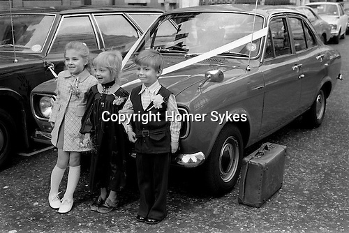 Children playing at just got married arm in arm having a photograph taken in front of 'going away' car. Old battered leather overnight suitcase waiting to be pit into car. London UK 1970s...