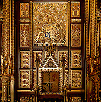 The Throne and, behind it, the Cloth of Estate, which symbolises the monarch. Despite its name, the Cloth of Estate is made of carved wood, largely covered in 24-carat gold leaf