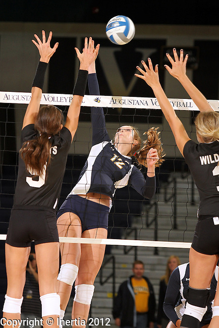 SIOUX FALLS, SD - SEPTEMBER 18:  Holly Hafemeyer #12 from Augustana tries to split the defense of Lauren Sieckmann #9 and Lexi Malm #3 from Wayne State in the first match of their game Tuesday night at Augustana. (Photo by Dave Eggen/Inertia)