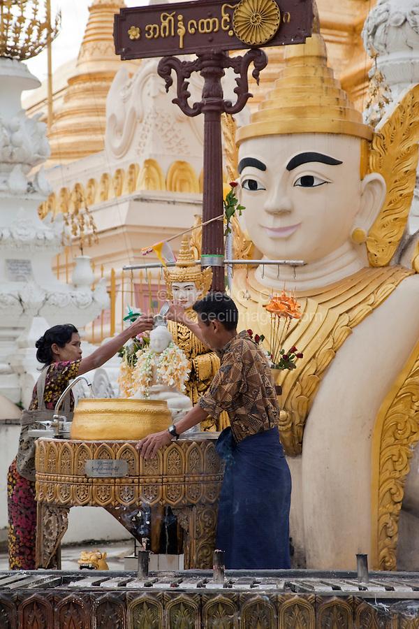 Myanmar, Burma.  Shwedagon Pagoda, Yangon, Rangoon.  Worshipers pour water, a sign of purification, over small Buddha.
