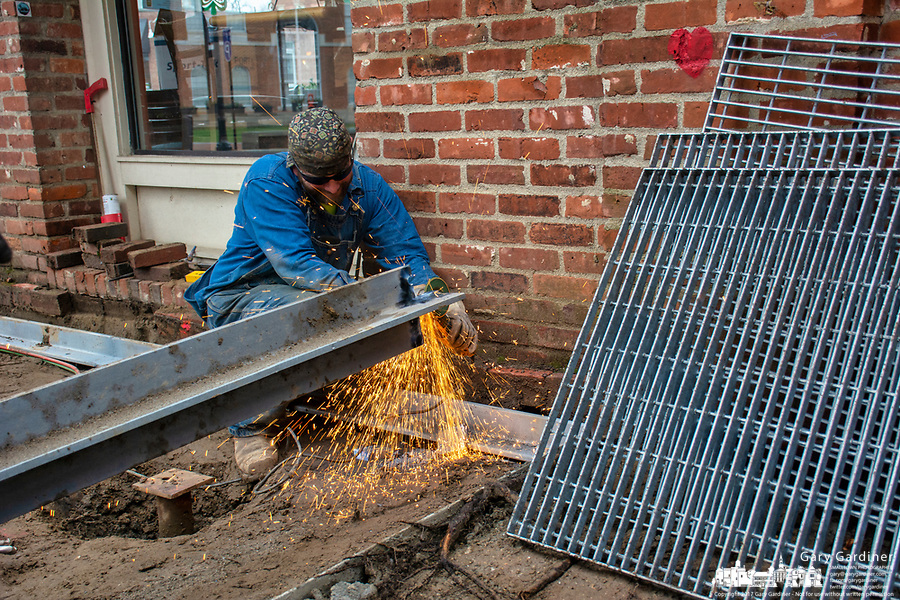 Welder grinds surface of steel beams that will be used to support a grate structure beneath the new brick walkway around the heritage oak tree next to Java Central.