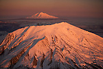 The snow-covered crater of Mount St. Helens in the foreground with Mt. Adams in the distance, Washington