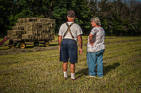 Sam Bigham and his wife, Connie, talk after loading a trailer with fresh hay recently baled on his family's Westerville, OH, farm. Bigham's family has owned the farm since 1920 but recently signed a contingency contract to sell the land to a housing developer. It is the last working farm in the city.