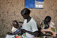 Two women with their babies queue to vote at a polling station in Malakal, South Sudan. On 9th January 2011 Southern Sudan's people voted in a referendum on whether to become independent from the North..