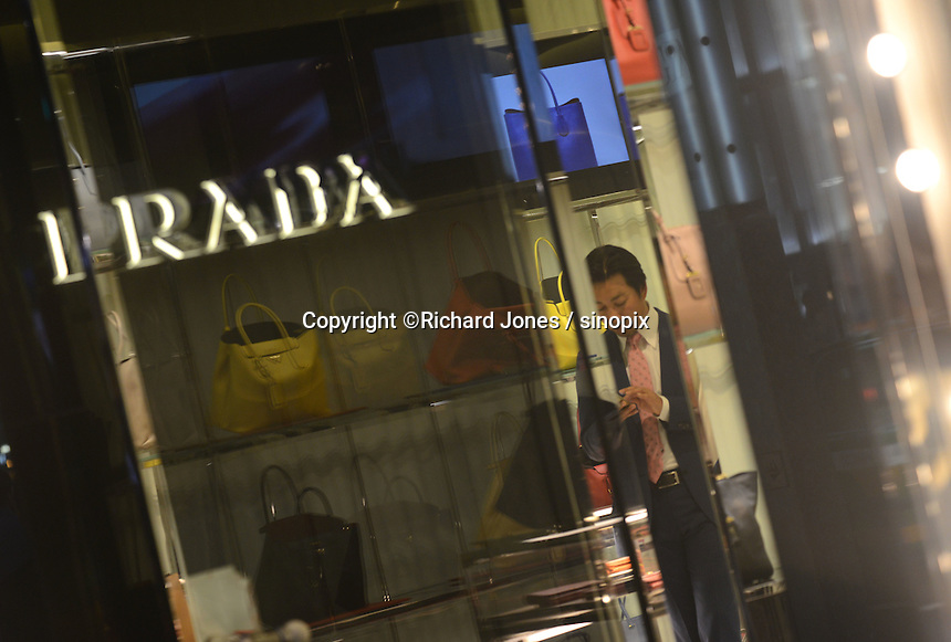 Shop assistant in front of Prada in the up-market shopping district,  Ginza, Tokyo, Japan.<br /> April-2014