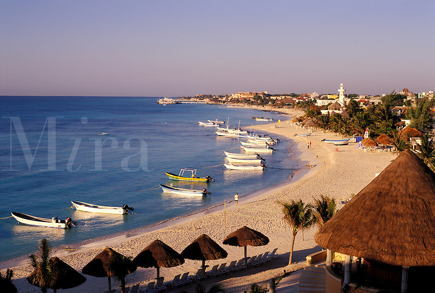 Mexico, Playa del Carmen. Beach scene with palapas, fishing boats and Caribbean Sea. Also known as the Mayan Rivera or Mayan Coast