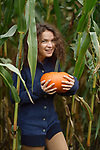 Portrait of a young smiling woman holding a pumpkin at a farm corn field, British Columbia, Canada, autumn harvest