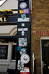 Supporters football stickers attached to a lamppost on Ealing Road outside the Princess Royal pub before Brentford hosted Leeds United in an EFL Championship match at Griffin Park. Formed in 1889, Brentford have played their home games at Griffin Park since 1904, but are moving to a new purpose-built stadium nearby. The home team won this match by 2-0 watched by a crowd of 11,580.