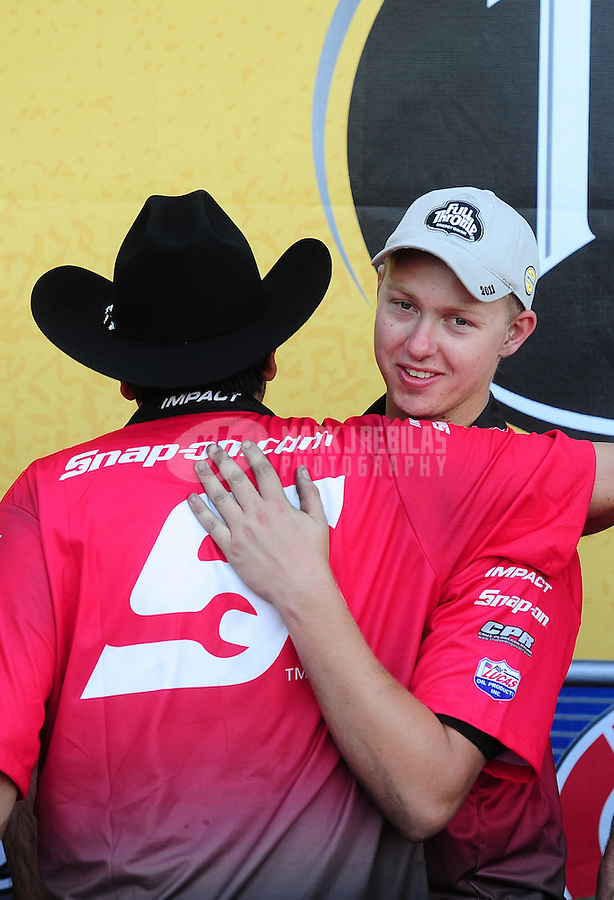 Sept. 25, 2011; Ennis, TX, USA: NHRA funny car driver Cruz Pedregon celebrates with crew members after winning the Fall Nationals at the Texas Motorplex. Mandatory Credit: Mark J. Rebilas-
