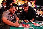 Jan Van Dyk bags his chips and writes down his chip count at the end of play