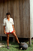 Acre, Brazil. Rubber tapper wearing rubber shoes with his foot on a ball of smoked rubber outside his house.