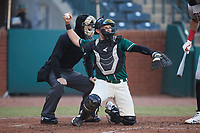 Greensboro Grasshoppers catcher Grant Koch (23) throws the ball back to the  pitcher as home plate umpire Adam Pierce looks on during the game against the Hickory Crawdads at First National Bank Field on May 6, 2021 in Greensboro, North Carolina. (Brian Westerholt/Four Seam Images)